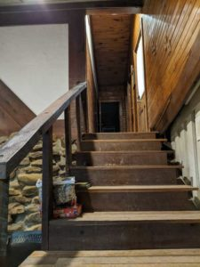A wooden staircase leads to the public restrooms upstairs